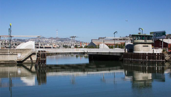 View of Islais Creek and bridge, with Sutro Tower in distance
