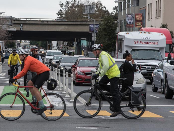 cyclists and cars at an intersection
