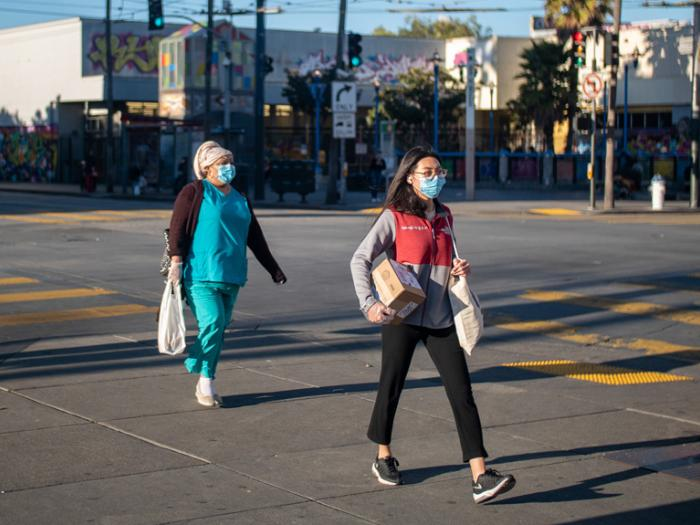 Two women wearing protective masks walking at crosswalk on 16th Street in the Mission District